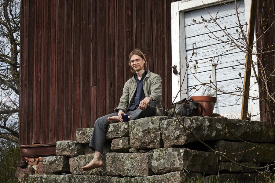 Jonimatti Joutsijärvi istuu vanhan aitan portailla. Kuva: Riku PIhlanto