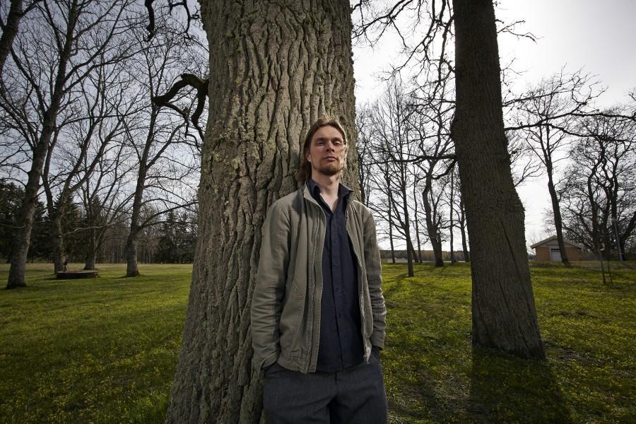 Jonimatti Joutsijärvi nojaa vanhaan tammeen Saaren kartanon puistossa. Kuva: Riku Pihlanto
